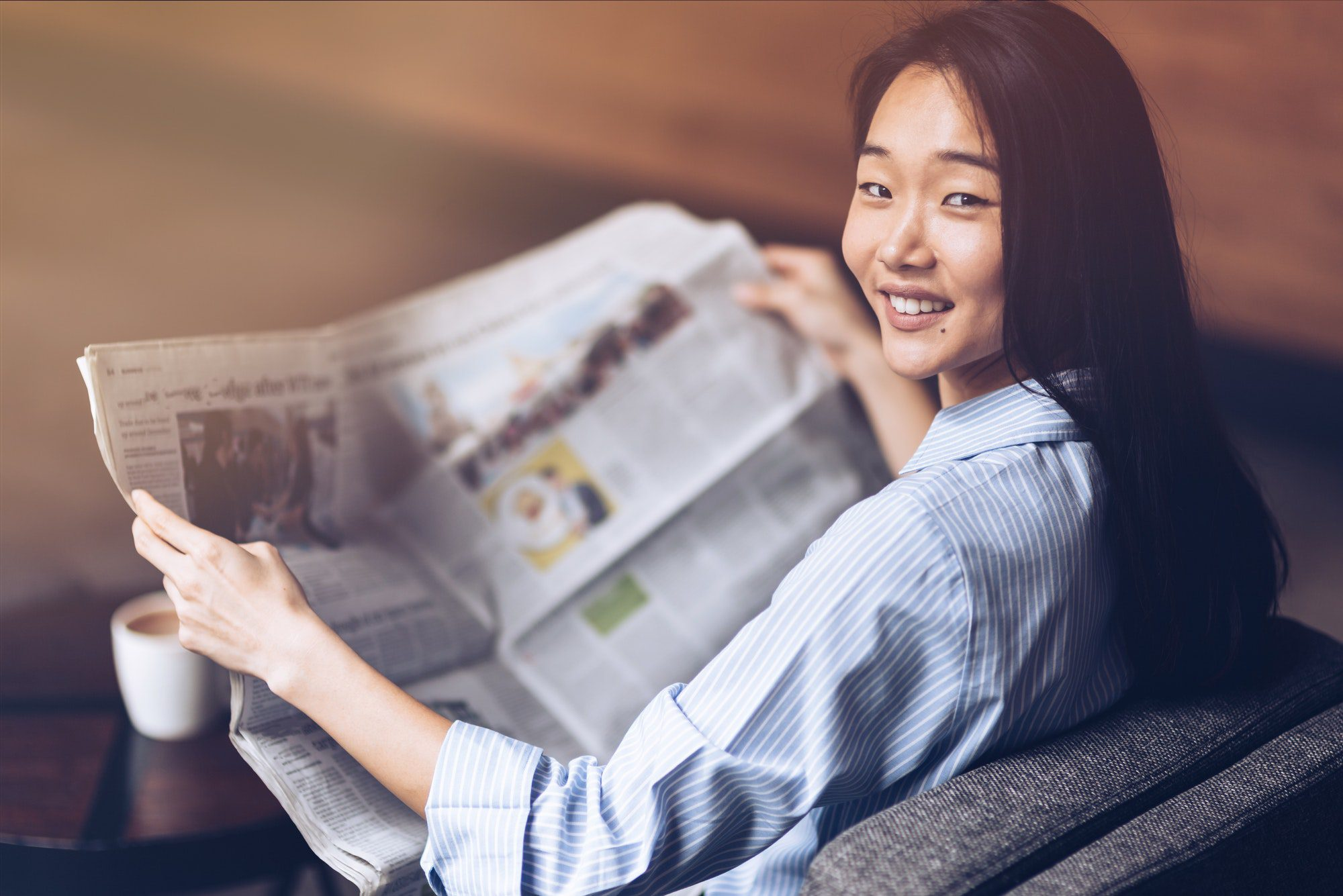Stay Current. Asian Business Woman Reading Newspaper And Drinking Coffee In The Morning In Cafe
